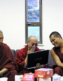 On a break for tea, Tibetan Buddhist monks Yeshi Tsultrim (left), Tenzin (center) and Kalsang Gyatso laugh at a video on a laptop in the Houston memorial Chapel at Randolph College in Lynchburg, Va., October 24, 2011.   (Photo by Parker Michels-Boyce/The News & Advance)